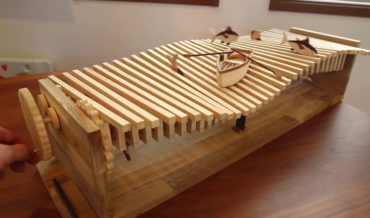 A Beautiful Kinetic Sculpture Of A Boat Bobbing Up And Down On Wooden Waves