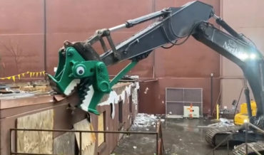 An Excavator Painted Like A Dinosaur Head With Googly Eyes Eats A Building