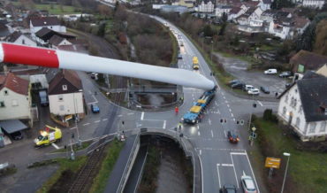 Aerial Shots Of A Tractor Trailer Hauling A 220-Foot Wind Turbine Blade At An Angle