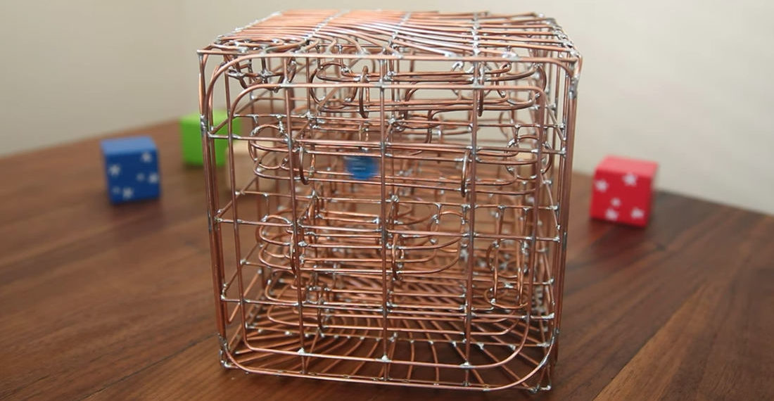 A Marble Maze Inside A Bent Copper Wire Cube