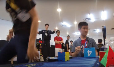Puzzler Solves Rubik's-Style Cube With Lightning Speed, Confuses Guy Timing