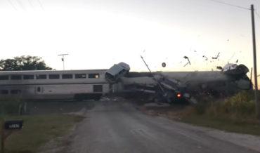 Train Hits Car Hauler Stuck On Tracks, Cars Go Flying