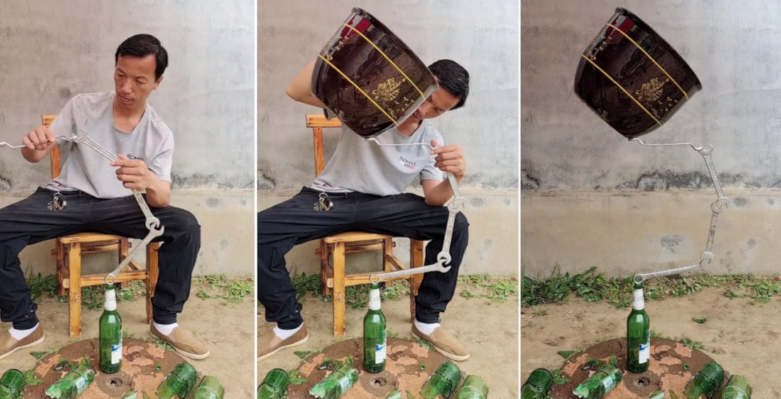 Man Precariously Balances Planter On Wrenches Resting On Top Of Glass Bottle